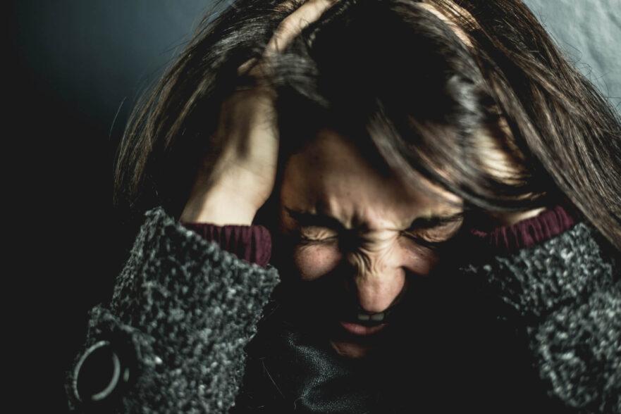 Woman holding her head migraine vs. headache